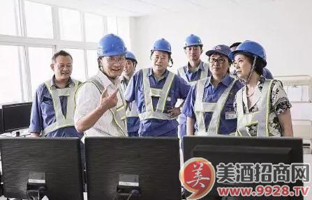 董事长孙明波(左二)在工厂与员工讨论生产经营情况。